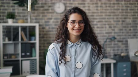 jó hangulatban : Portrait of beautiful female employee looking at camera and smiling standing in office alone during workday. Happy people, successful business and workspace concept. Stock mozgókép
