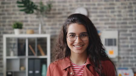 fejlövés : Slow motion portrait of pretty girl happy employee smiling and looking at camera in modern loft style office expressing positive emotions. Youth and workplace concept.