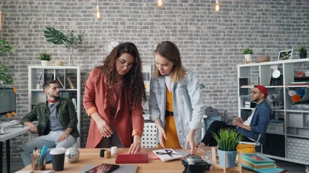 kreatywne : Creative designers attractive women are organising things on desk to shoot flat lay in office during work day in designing agency. Photograph and technology concept. Wideo