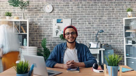proprietário : Zoom out time-lapse of happy successful young man smiling looking at camera in office room siting at desk when employees are moving around. Business and youth concept. Vídeos