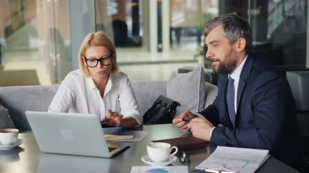 формальный : Mature business lady is discussing information on laptop screen with bearded man sitting at table in modern cafe talking. Conversation and partnership concept.