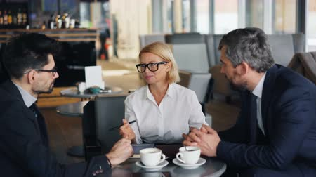 açıklama : Cheerful business lady with blond hair is negotiating agreement with male partners bearded men during meeting in cafe. Talks, communication and work concept.