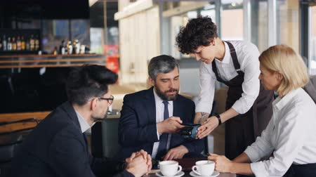 официант : Entrepreneur is paying for business lunch in cafe using smartphone and talking to coworkers sitting at table together. Modern technology and payment concept.