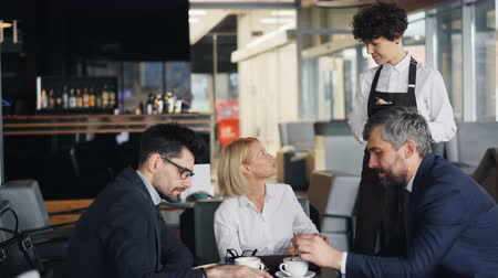 официант : Waitress in apron is taking order from group of businesspeople middle-aged men and lady talking sitting at table. Communication, lunch and work concept.