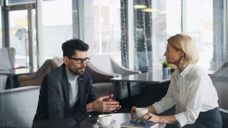 неформальный : Successful businessman is talking to attractive mature woman coworker in cafe sitting at table together speaking gesturing and smiling. Business communication concept. Стоковые видеозаписи