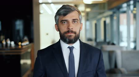 стремление : Portrait of attractive bearded man with gray hair businessman looking at camera with serious face standing in cafe alone. Businesspeople and lunch break concept.