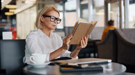 alfabetização : Attractive mature business lady in glasses is reading interesting book during lunch break in cafe. Self-education, literature, intelligent people and leisure concept. Vídeos