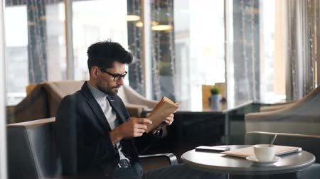 roman : Intelligent businessman bearded man in glasses is reading book turning pages sitting in cafe alone enjoying novel. Literature, hobby and free time activity concept.