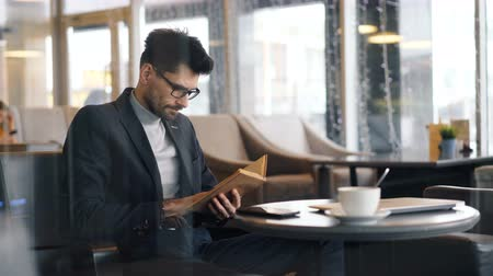 alfabetização : Entrepreneur bearded dark-haired man is focused on reading interesting book sitting in cafe waiting for meeting. Leisure time activity and business concept.