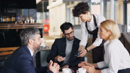 garçonete : Bearded man in suit is making online payment in cafe paying for business lunch then talking to coworkers discussing work. Electronic money and businesspeople concept.