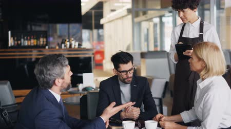 cortes : Group of coworkers men and woman are talking to waitress in cafe making order during lunch break in business center. Communication and coffee house concept. Vídeos