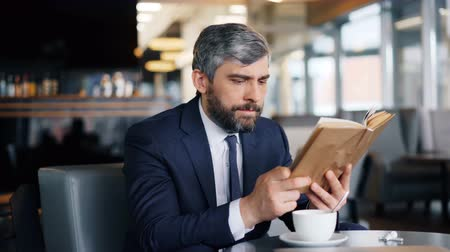 alfabetização : Smart entrepreneur mature bearded man is reading book sitting in cafe alone enjoying interesting story during coffee break. Literature and business people concept. Vídeos