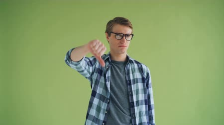 hanyatlás : Portrait of disappointed young guy in trendy outfit showing thumbs-down and shaking head on green background. Unsatisfied people and emotions concept.
