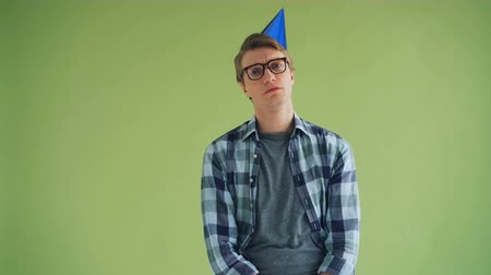bad mood : Portrait of unhappy young man in bright party hat looking at camera with sad face standing alone on green background. Birthday, loneliness and sadness concept.