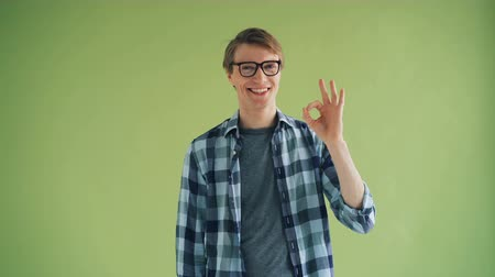 jóváhagyás : Portrait of cheerful young man showing OK gesture and smiling looking at camera standing on green background. Approval, human reactions and people concept.