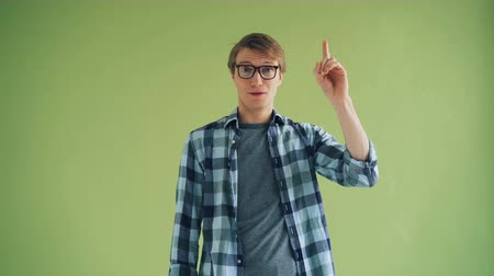 genius : Portrait of smart guy in glasses having great idea raising finger and smiling looking at camera standing on green background. People and gestures concept. Stock Footage