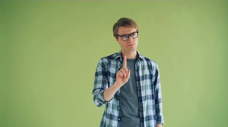 denying : Portrait of serious guy hipster shaking head and waving finger showing no gesture standing on green background. Youth, human reactions and people concept. Stock Footage