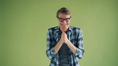 intrigue : Portrait of sly young man in glasses rubbing his hands and smiling looking at camera with cunning face standing on green background. People and emotions concept.