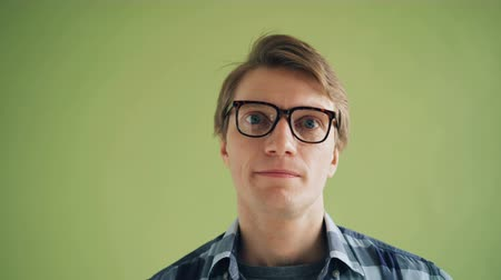 doubt : Close-up portrait of puzzled young man rolling his eyes wearing trendy glasses on green background. Human emotions, attractive people and feelings concept.