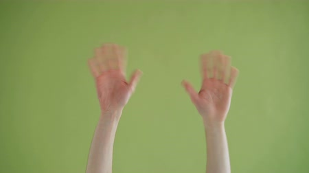 nonverbal : Close-up shot of male human hands appearing then waving hello and disappearing in green background. Gesture, communication and friendly greeting concept. Stock Footage