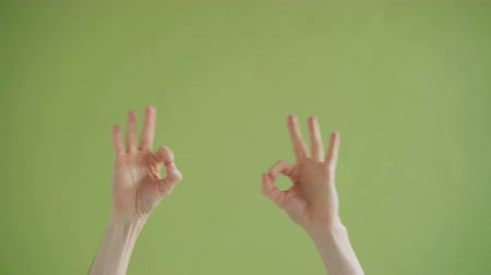 close cropped : Close-up shot of human male hands making v-sign then OK gesture moving dancing against green background. Persons body, fun and joyful gesturing concept. Stock Footage