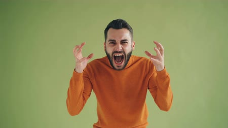 zangado : Portrait of mad young man screaming looking at camera with rage standing on green background raising arms. Negative emotions, anger and people concept.