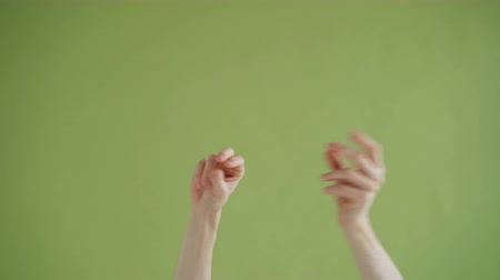 nonverbal : Close-up shot of human mans hands snapping fingers then moving in funny rhythm on green background. Fun, good mood, arms gesture and people concept.