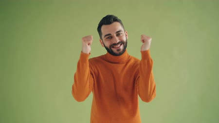 jóváhagyás : Portrait of happy satisfied man in trendy sweater showing thumbs-up and smiling standing on green background. High evaluation and joyful youth concept. Stock mozgókép