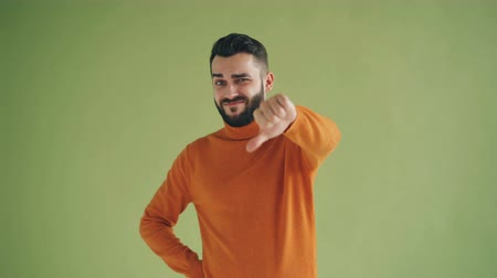 хмурый : Portrait of unhappy hipster unsatisfied customer showing thumbs-down gesture looking at camera standing on green background. People and emotions concept.