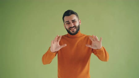 incerteza : Uncertain guy showing so so sign then thumbs-down hand gesture and frowning face standing against green background. People, attitude and dislike concept.