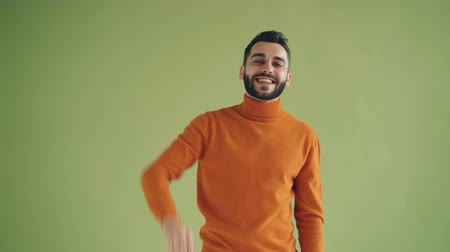 saying : Portrait of handsome male student waving hello then showing come here gesture inviting friend to join standing on green background alone. Youth and greeting concept. Stock Footage