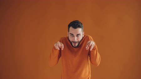 гримаса : Portrait of silly young man making funny faces and laughing having fun looking at camera standing against orange background. Crazy people and joy concept.