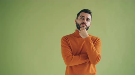 pensamento : Portrait of good-looking guy thinking touching beard then having good idea raising finger standing alone on green background. People and thoughts concept.
