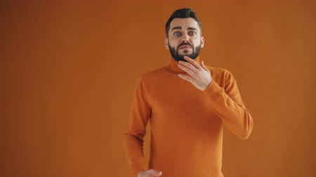 devastated : Portrait of upset bearded person feeling bad after unpleasant surprise standing on orange background. Negative emotions, disappointment and youth concept.
