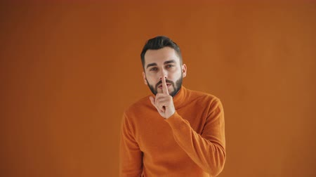 シャット : Portrait of handsome young man making shush gesture touching mouth with finger asking for silence standing against orange background wearing bright sweater.