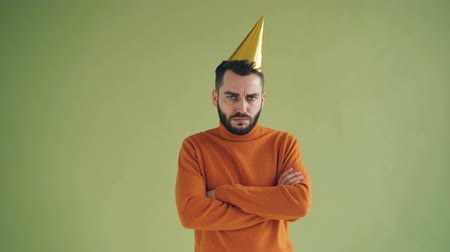 miserável : Portrait of upset young man in bright party hat standing alone with arms crossed sighing and shaking head feeling lonely and unhappy on birthday. People and holidays concept. Stock Footage
