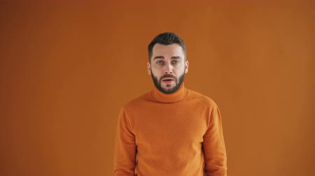 influenza background : Portrait of bearded guy sneezing then wiping nose and smiling looking at camera standing against orange background. People, influenza and bad health concept. Stock Footage