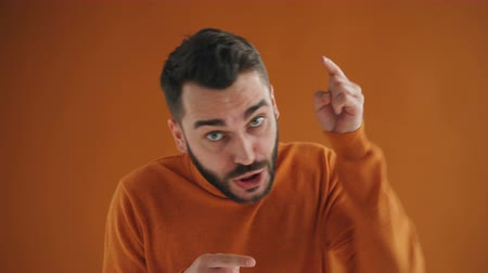 odino : Portrait of angry bearded guy shouting and pointing at camera fighting expressing anger standing alone on orange background. People and conflict concept.