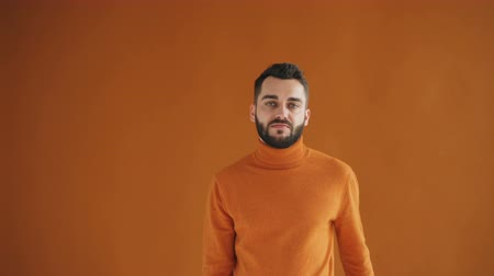denying : Portrait of attractive bearded guy waving finger and shaking head saying no standing on bright orange background. Youth, human reactions and people concept.