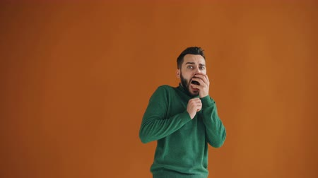 údiv : Portrait of frightened young man looking at camera with fear and gesturing standing against orangebackground. Scared people and negative reactions concept.