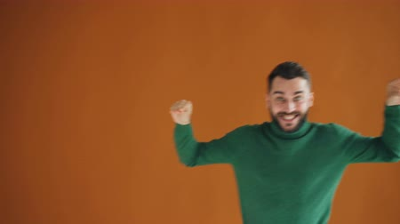 コミカル : Portrait of silly bearded guy dancing away making funny hand gestures and smiling moving against bright orange background. Millennials and joy concept. 動画素材