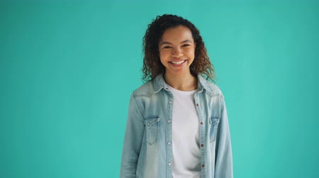 kıvırcık saçlar : Portrait of cheerful African American woman turning to camera and laughing standing alone against blue background. Pretty girl, joy and happiness concept.