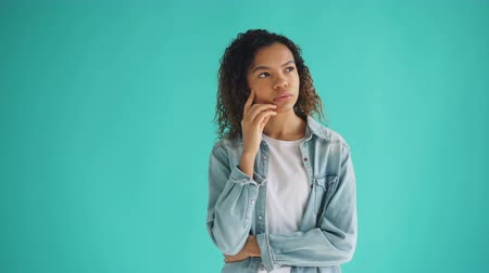 doubt : Portrait of thoughtful African American girl looking at camera on blue background thinking over problem making decision touching face. People and thoughts concept.