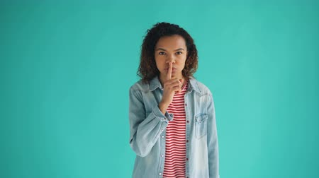 sigilo : Portrait of beautiful African American lady making shush gesture touching mouth with finger asking for silence standing against blue background. Youth and secrets concept. Stock Footage