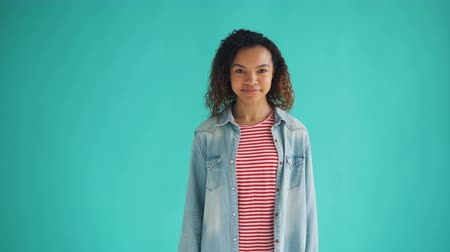 charisma : Portrait of beautiful African American student looking around then winking at camera and smiling flirting standing alone on blue background. People and relationship concept. Stock Footage