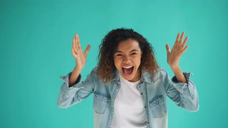 bad mood : Portrait of angry African American lady screaming then standing with arms crossed on blue background feeling mad and irritated. Human emotions and youth concept. Stock Footage