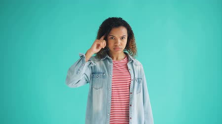 anlamı : Portrait of African American lady twisting finger at temple making fool sign looking at camera standing alone on blue background. People and attitude concept.