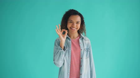 jóváhagyás : Portrait of glad African American girl showing OK hand gesture looking at camera and smiling standing against blue background. Millennials and evaluation concept. Stock mozgókép