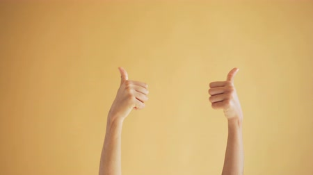 értékelés : Close-up shot of womans hands showing thumbs-up gesture on orange background expressing approval and high evaluation. Like sign and happy people concept.