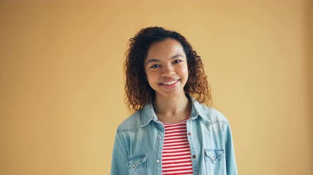 on camera : Portrait of good-looking African American girl in casual clothing walking to camera smiling looking at camera. Beautiful young people and good mood concept.